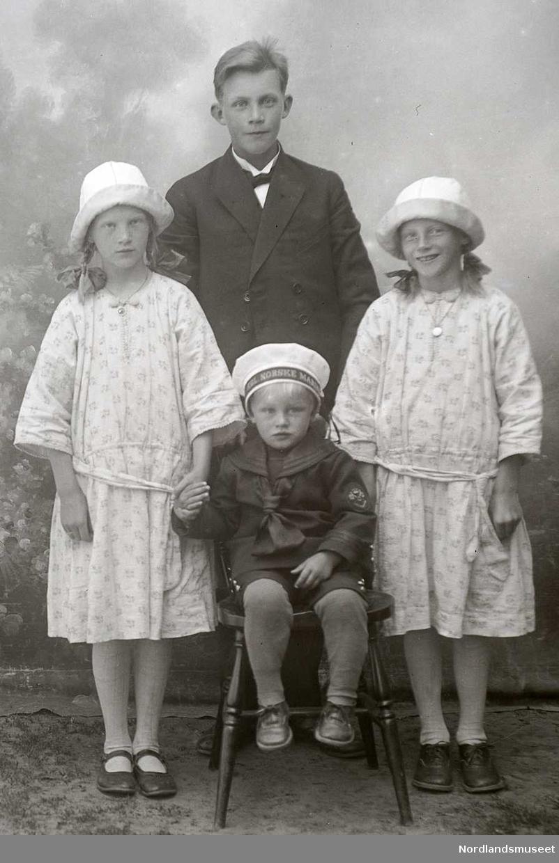 Portrett. 4 barn, ca. 4 - 12 år. Foran sitter et barn ca. 4 år. Ved siden står 2 jenter ca. 10 år i lyse klær og hatter. Har fletter. Jentene er muligens tvillinger. Bak dem står en gutt i tenårene, iført dress.