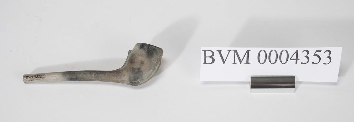 Krittpipe med en enkel dekor på pipehodet. På ene siden bokstavene TB. Pipen bærer preg av bruk og enden av munnstykket er knekt av.