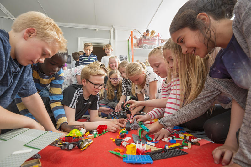 Skoleklasse leker med lego i leketøysutstilling