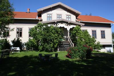 Kvinnemuseet med blomsterbed og sveitserstilveranda. Foto/Photo