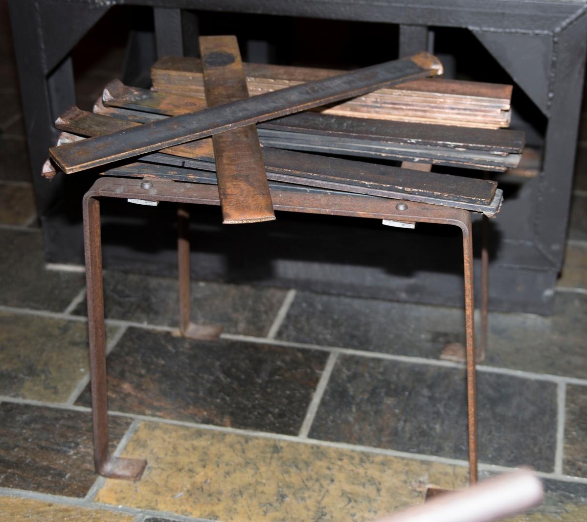 Flate jernplater montert sammen med stålnagler slik at de danner ett stativ med flat topp og fire bein. 15 teiner er montert på stativet.
