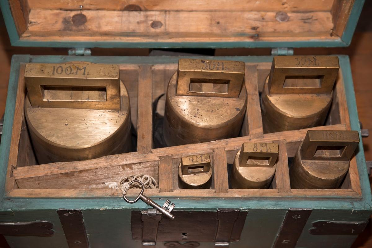 Rektangulær kiste som inneholder seks lodd og en nøkkel.