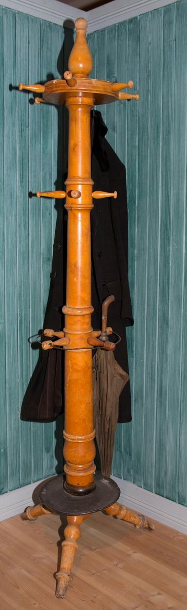 Stativet har en dreid trestamme som står på en fot. I tre ulike høyder på stammen stikker det ut rette knagger, til sammen 14 stykker. Foten består av en rund blikkplate over tre dreide bein