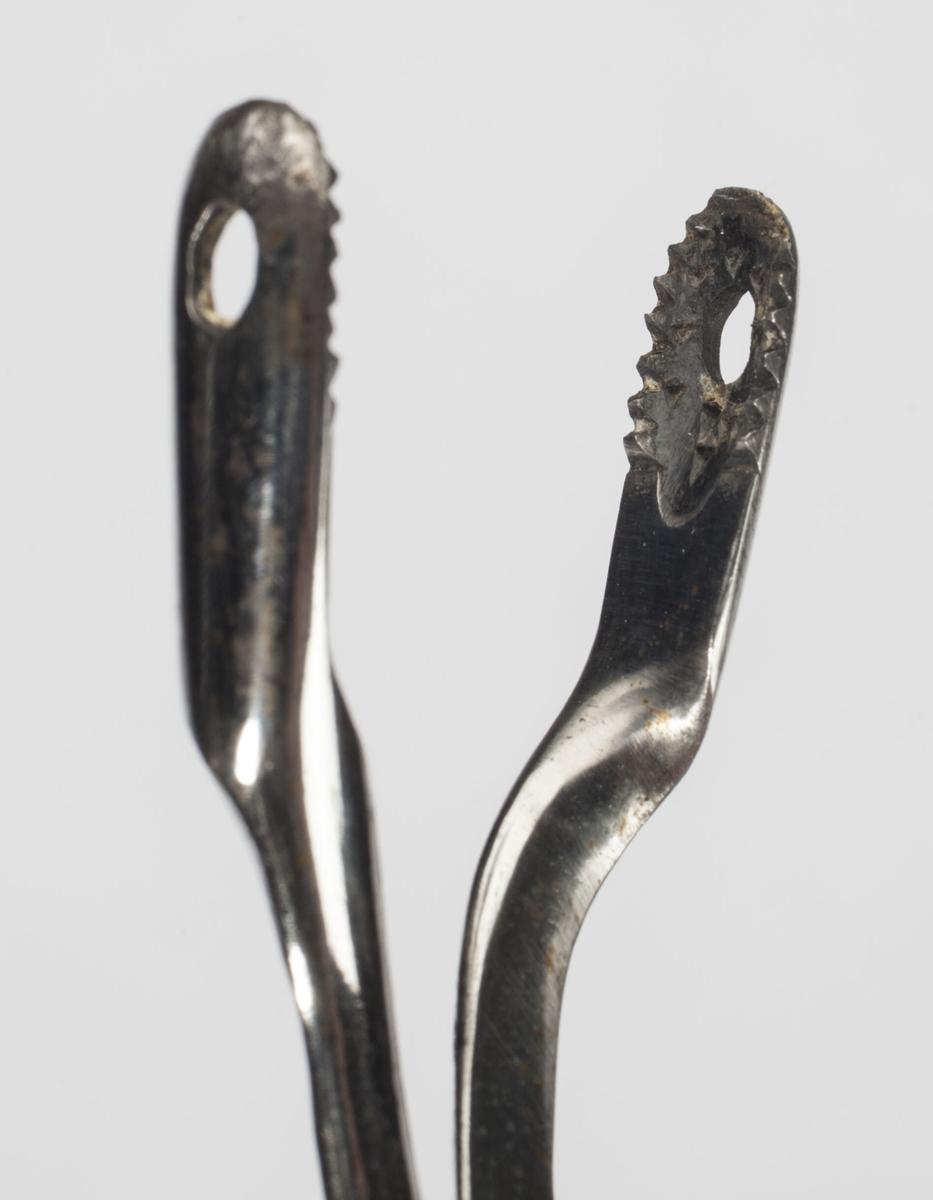 Instrumentet holdes i to ringer som en vanlig saks. I gripeenden er flatene riflet og med et hull.