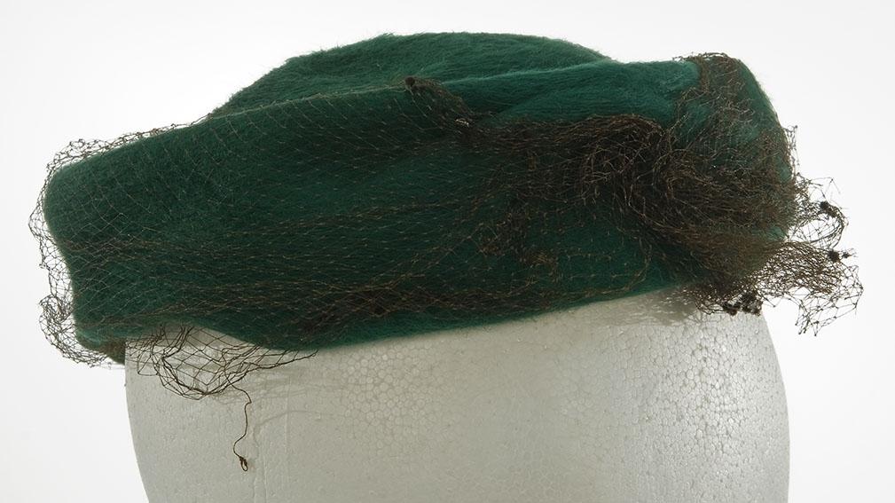 Flat, rund, liten hatt. Pyntet med lite perlebroderi og nett.
