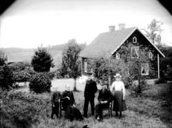 Familjegrupp 5 personer i trädgården.Parstuga.Viktor Larss