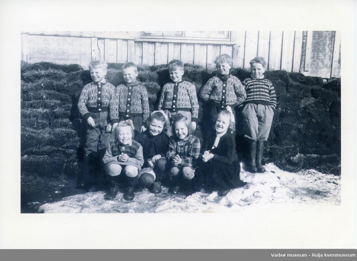 Første klasse i 1952 foran den gamle skolebygningen i Skallelv. Foran fra venstre Nelly Huru, Wally Johansen, Åse Snevoll, Randi Harjo. Bak f.v. Arnold Huru, Bjarne Rimala, Håkon Bauna, Kjell Harjo og Egil Sundelin.