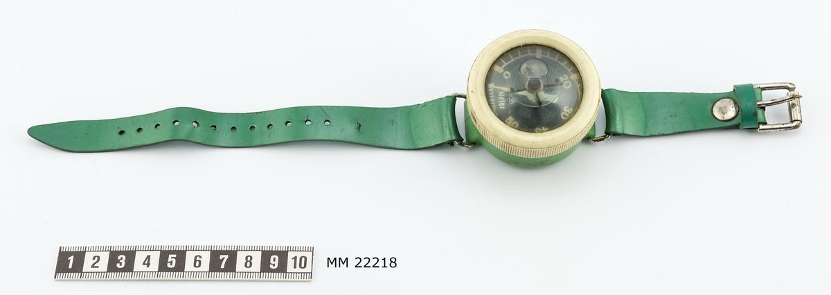 """Djupmätare, armbandsformat, av plast och glas. Ljusgrön och vit mätare. Mätaren har en skala graderad från 0-50. Märkt """"Meter Wassertiefe"""". På mätaren sitter även en liten kompass. Mörkare grönt armband i plast."""