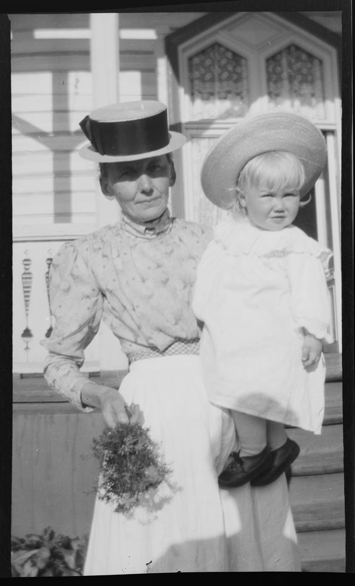 En kvinne bærer Iacob Ihlen Mathiesen på armen. I den andre hånden holder hun en bukett ville sommerblomster. Solen skinner.