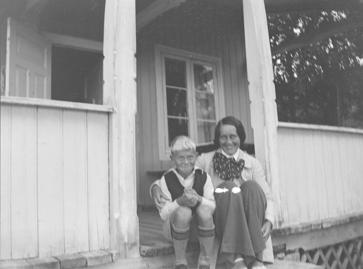 En gutt og en kvinne, Ole og Jil, sitter på trappen opp til verandaen til et hus i Jeppedalen. Begge smiler til fotografen. Døren fra verandaen inn til huset står åpen, det er sommer.