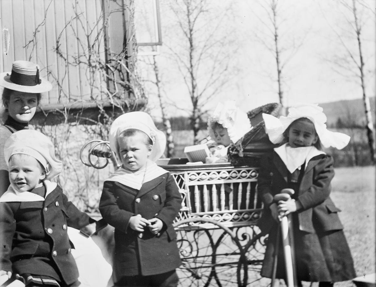 En kvinne med fire barn, hvorav et barn i barnevogn, sitter utenfor et hus som muligens er Mathiesens hus på Lunden. Barna er sannsynligvis fire av Christian Pierre Mathiesen og Celina Ihlen Mathiesens. Jenta lengst til høyre er Celina Marie Mathiesen.