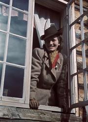 Tweedeklädd kvinna i hatt blickar ut genom ett öppet fönster