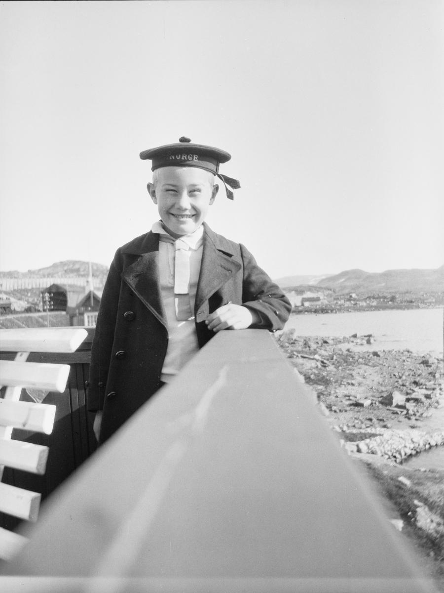 Iacob Ihlen Mathiesen står med armen hvilende på et rekkverk. Han har uniformslignende klær og noe som ligner en type matroslue med Norge skrevet med store bokstaver foran. Bak ham ligger et stasjonsområde som ligner på Haugastøl stasjon på Bergensbanen.