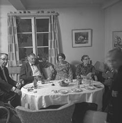 Midsommardans på Lövnäslogen, grupp runt bordet.
