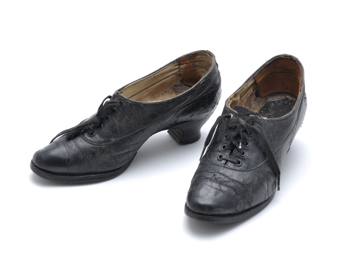 Svart lærsko med snøring. Halvhøy hæl med snelleform. Skoene er velbrukt, med sprekker og skader i læret.