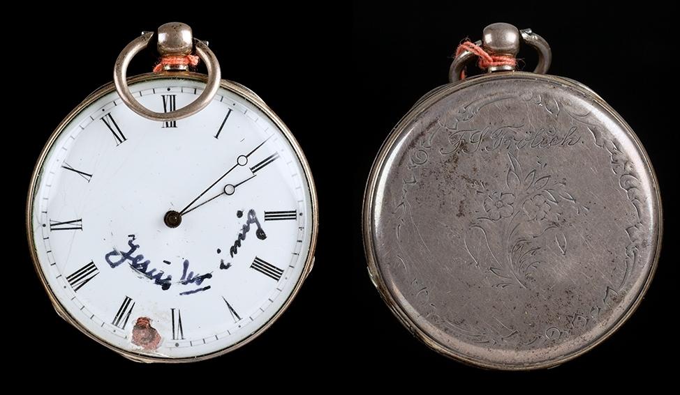 Sølv lommeur med bøyleopptrekk, har tilhørt F.S. Frølich. Inskripsjon: F. S. Frølich Tallskiven har romertall fra I til XII. Notert på tallskiven med håndskrift: Jesus bor i meg.