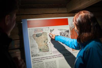 To voksne leser utstillingsplansje. Foto/Photo