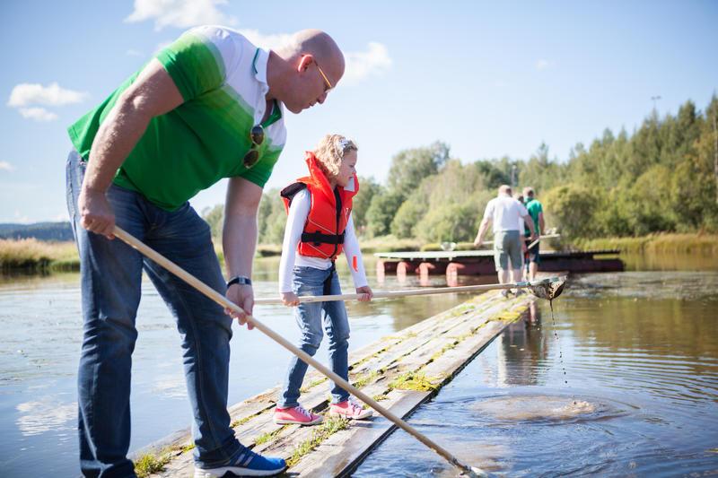 Foto av en far og datter som fanger insekter i vann