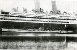 Torpedobåt ligger ved skipssiden til passasjerdamperen 'Berl