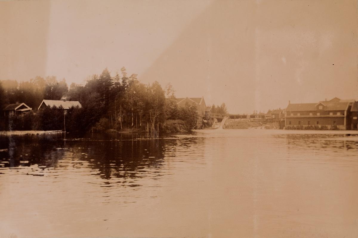 Landskapsbilde med vann i forgrunnen og et sagbruk i bakgrunnen.