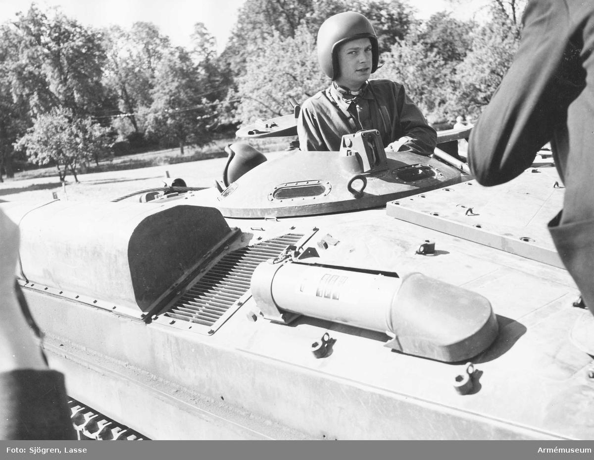 Dåvarande kronprinsen, senare kung Karl XVI Gustaf, sticker upp huvudet ur en lucka till pansarfordon, förmodligen en stridsvagn 103 S, 1960-tal.