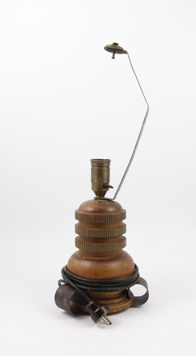 Tre elektriske bordlamper designet av Thilo Schoder. A: Høy smal fasong, fire små føtter, høy smal hoveddel, støpsel til to lyspærer i nedad hengende retning, spir på toppen trolig til feste av lampeskjerm B: Tre føtter i smijern kommer ut på siden, robust hoveddel med malt vertikal dekor i fordypninger i treverket. Lang metalldel på toppen, trolig til eventuell lampeskjerm, feste til en lyspære i hoveddelen. C: Fire små bein, bred bunn, bulket smal stake opp til lyspærefestet. Trolig tiltenkt lampeskjerm festet direkte på lyspæren. Ledning fra bunnen i alle tilfeller.