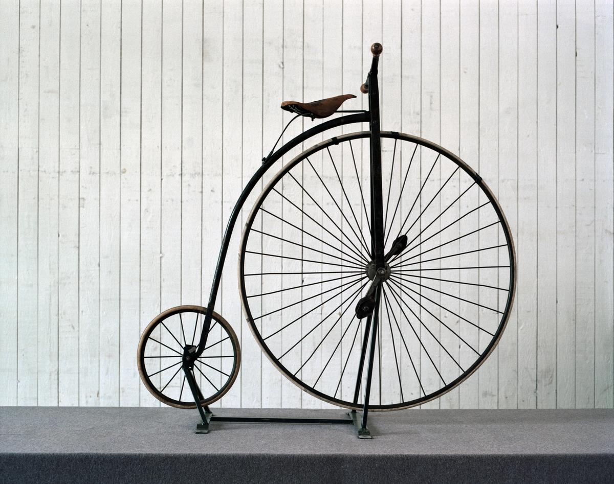 Höghjulig, mindre modell, med framgaffel av plattjärn och originalgummi på bakhjulet. Tillbehör: Ringklocka och verktygsväska.