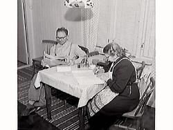 Maria ich Knut vid köksbordet. Maria skriver brev till sin b
