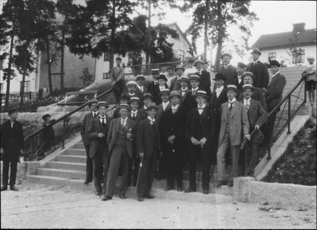 Bild visande skråverksamhet. Gruppbild av män, guldsmeder, på trappa.