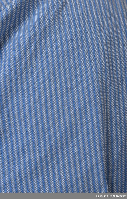 """Livørsbusserull med linning i halsen og langs nedre kant. Knapping helt ned foran. Kypertvevet bomullstoff - Blått/hvitt/svart (nå grått) stripet. Fra Hoffsbro veveri. Ponchosnitt, dobbelt stoff over skuldrene. Rett, glatt isydde ermer med kile under """"ermspjeld"""". Svarte knapper. Legg langs linningen i ryggen. Stoff fra Hoffsbro veveri. Innerlomme. Hjemmesydd."""