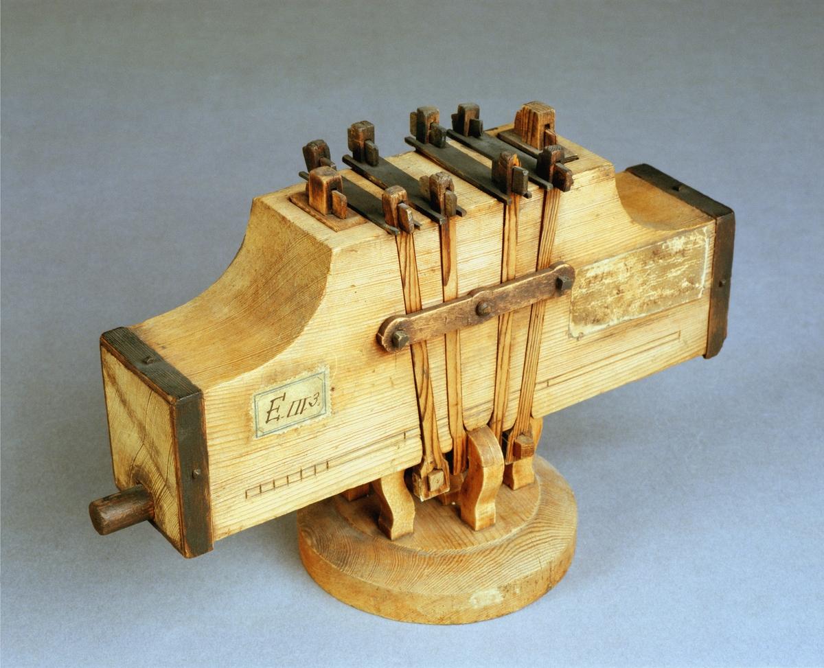 """Modell av klockaxel, från senare hälften av 1700-talet. Text på föremålet: """"N:o 186. .... Klåckaxeln ...... Af Presid:etc Gr: Cronstedt. E.III.3"""".  I Jonas Norbergs förteckning från 1779 beskrivs modellen på följande sätt: """"Modell på Klock=axel, utvisande huru den rätt bör beslås."""""""