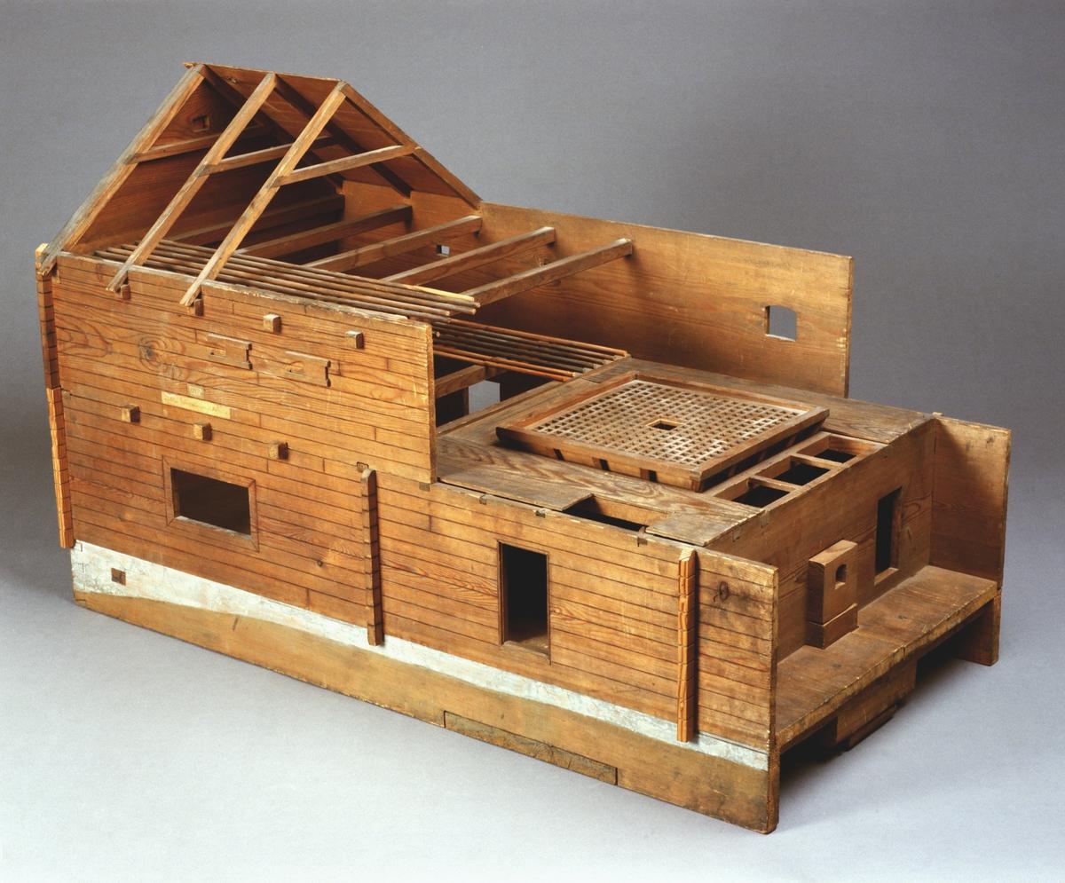 """Modell av torkria. Text på föremålet: """"N:o 128. Modell af Rijan på Frösunda. Tillhör Fysiska kabinettet. N:o 6. XVI.E.3"""". I Jonas Norbergs förteckning från 1779 beskrivs modellen på följande sätt: """"Modell på en Rija, med dels ugn och torcklafva, byggd på Frösunda, nära vid Stockholm. Husets skapnad liknar en vanlig loge, med dess tvenne sädesgålf: men mitt uti är istället för loge, anlagd en ugn, med dess torcklafva ofvanpå, til renkastad säds torckning: och uti hvardera av de 2.ne sädesgålfven, äro 2 hvarf  bjälckar ofvanpå hvarandra, med pålagde stänger, uppå hvilka den nyss inbärgade säden sättes at torckas. Nedersta bjälcklaget ligger til den höjd, at man kan tröska derunder efter vanliga sättet med slagor på trägålf."""""""