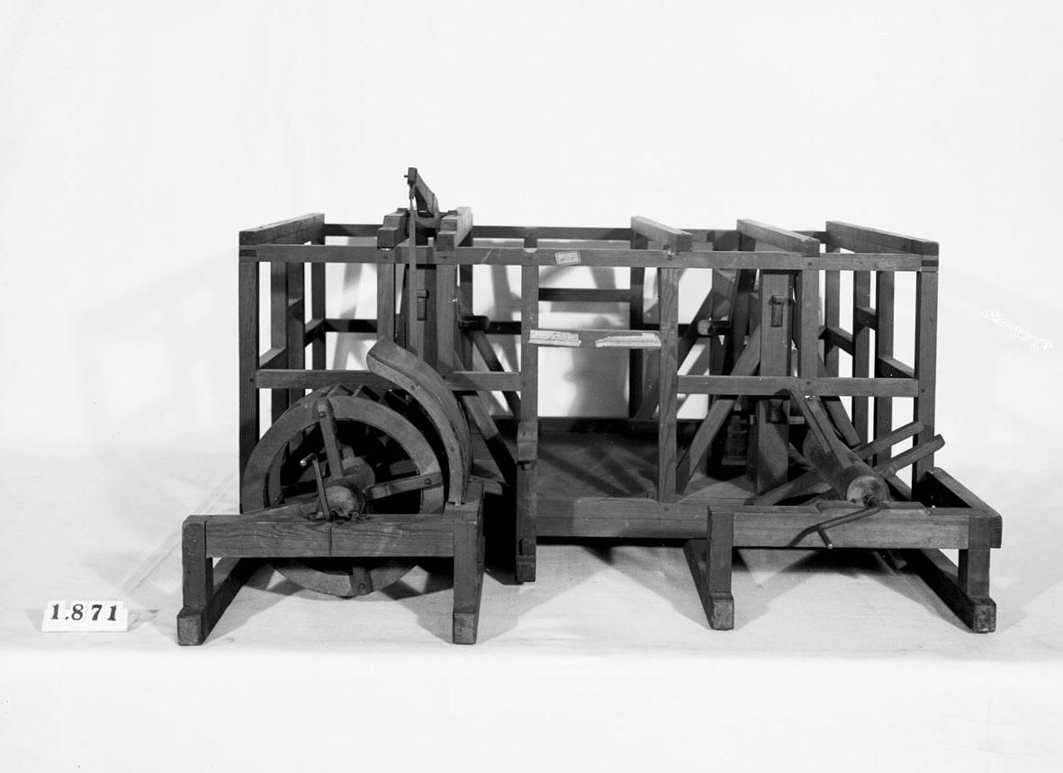 """Modell av två olika slag av stångjärnshammare. Text på föremålet: Modell å 2 olika ... stångjernshammare. A-z-3"""". I Jonas Norbergs förteckning från 1779 beskrivs modellen på följande sätt: """"Modell tilförkortande af de vanlige hjulstockar i Hammar-Smedjor, af Kongl. Secreteraren Herr Christiernin."""""""