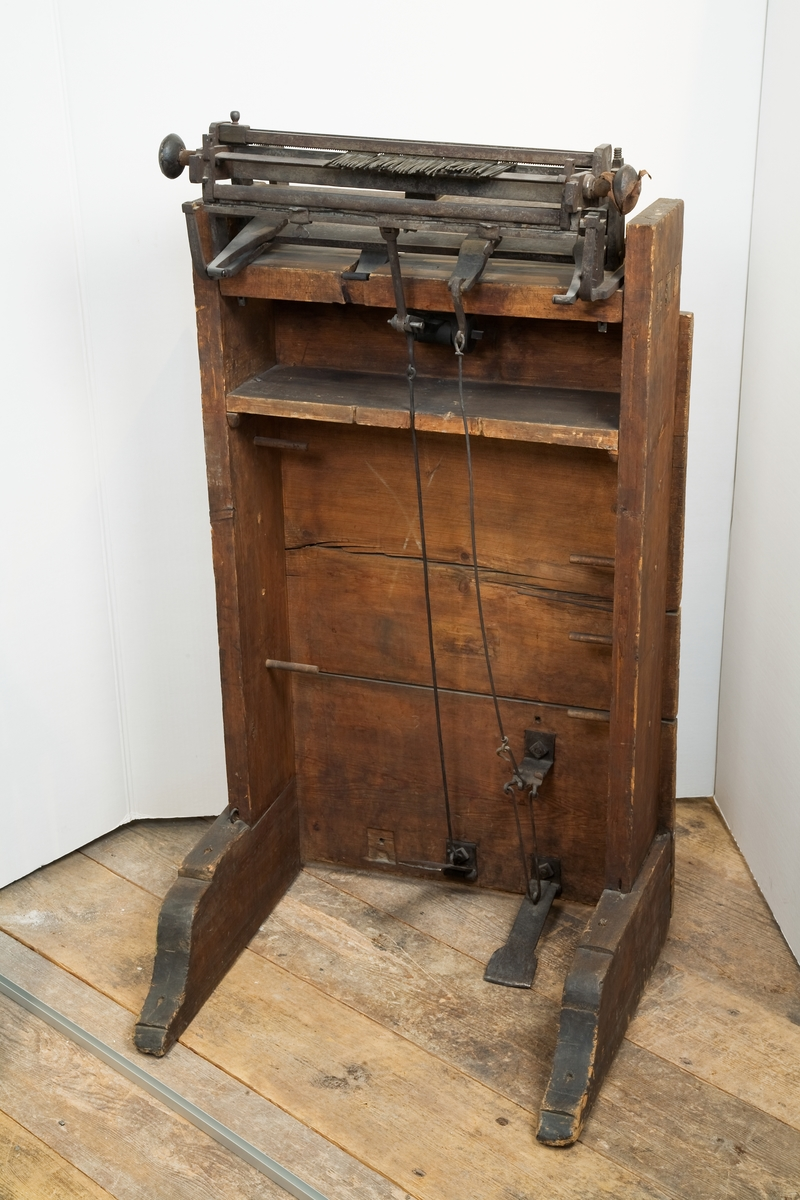 """Strumpvävstol, sammankopplad med garnvinda. Text på föremålet: """"N:o 15. ....väfstol. Af Hrr Rid: och Comend: af Kongl. Nordst: orden Polhem. N:o 5""""."""