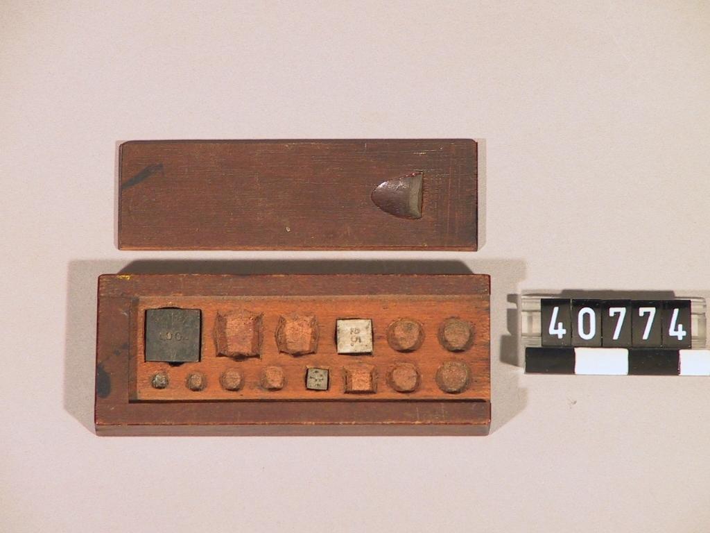 Brun träask med skjutlock. Asken har plats för 14 vikter. T re vikter finns med markeringarna 100, 25 sesp 4.