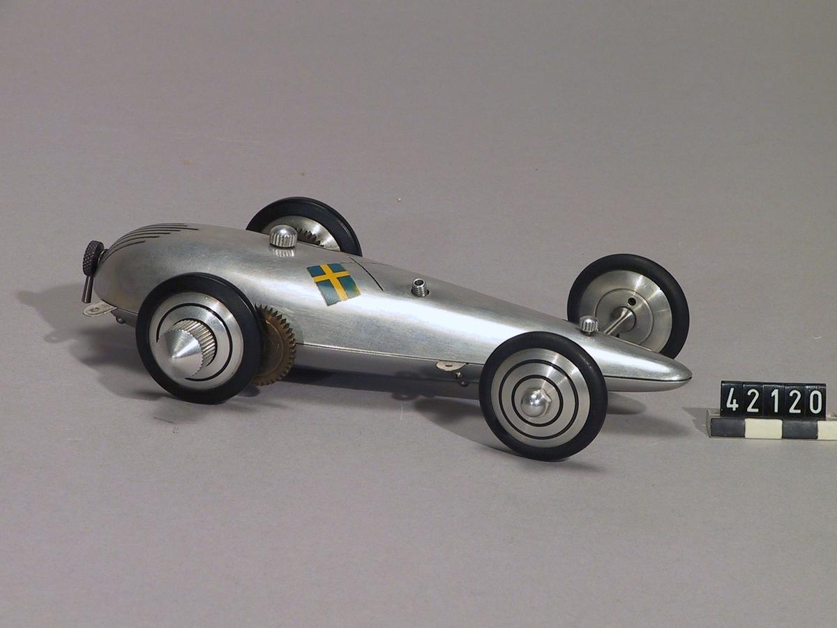 Precisionsbygge i lättmetall och aluminium. Motorn drevs med en blandning av eter och oljor. Modellen är avsedd att köras i en cirkelbana på plant golv, förankrad med en lina i centrum.  Encylindrig dieselmotor, cylindervolym ¼ cc, effekt 1/86-dels hk vid 16 000 varv/minut. Tillbehör: Trälåda med plexiglaslock, tratt, extra däck, 2 skruvar, 2 plåtbitar, hjulbult, gummipackning, ridningsartikel från 1947 samt foto på Harry Fjellström.