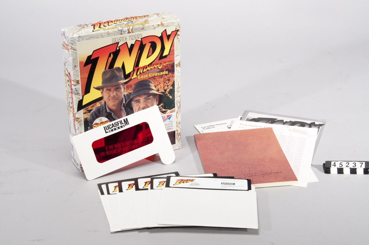 Indiana Jones and the Last Crusade: The Graphic Adventure. Datorspel för PC. Spelet är förpackat i en ask och omfattar sex stycken floppydisketter. Medföljer gör även manual, en översättnignstabell, samt en bok med bilagor till spelet. Spelet är ett äventyrsspel som spelas i tredjeperson perspektiv och är inriktat på problemlösning med vissa actioninslag.  För PC, XT, AT, PS/2, Tandy