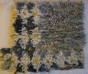 Mattprov i ryateknik. Olika grå nyanser, något gult samt grönt och gult runt mattans kanter. Mönsterskiss finns KLH. D2:412, Vävt på Önnestads mattväveri. Se inv.nr 1022 för annan färgställning.