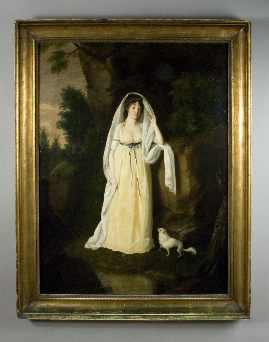 Porträtt av kvinna i helfigur, Fredrika Charlotta Stenbock, Lolotte, klädd i  gulvit empireklänning stående vid en klippa. Vid hennes fötter en liten vit hund. Skog i bakgrunden.