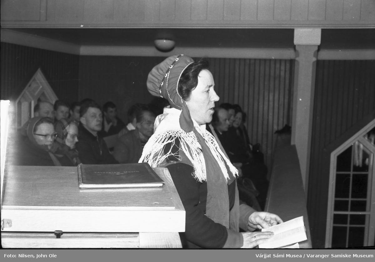 Marie Varsi synger i Nesseby kirke. Hun var en flink og anerkjent sanger(inne) i det samiske miljøet.  Bildet er tatt på galleriet i Nesseby kirke. 1967.