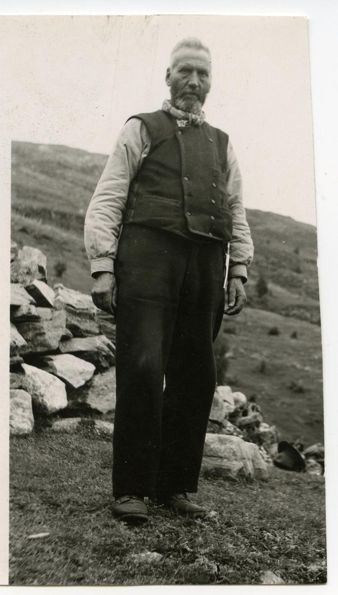Portrett i helfigur av en mann som står foran en steinmur. Mannen er iført vest, mørke bukser og et halstørkle. Hatten ligger på bakken i bakgrunnen.