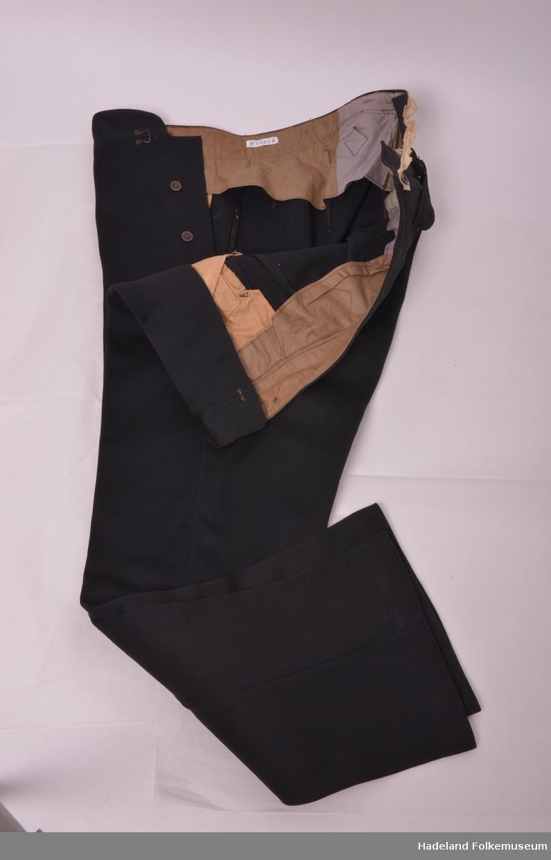 Frakk og bukse, Brudgomsdress. Svart ullstoff, klede.  a) Frakk fóret med svart bomullssatin. Ermene fóret med gråbrunt bomullsstoff. Skjøtene har sårkant ned. Lommer i splitt bak. Enkeltspent med nedbrettet krage og slag. 3 slåtte knapper. Høyde 94cm Hånd og maskinsøm. Innerlomme på venstre forstykke. 2 knapper bak.  b) Langbukse med utvidelse med (X) av annet stoff bak. Splitt og spensel. Sekundær lerretshempe. Lommer med strikning på forstykkene. Gylf. Buksebein skrår itt ut nederst. Høyde 108cm 6 knapper på retten på linningen.