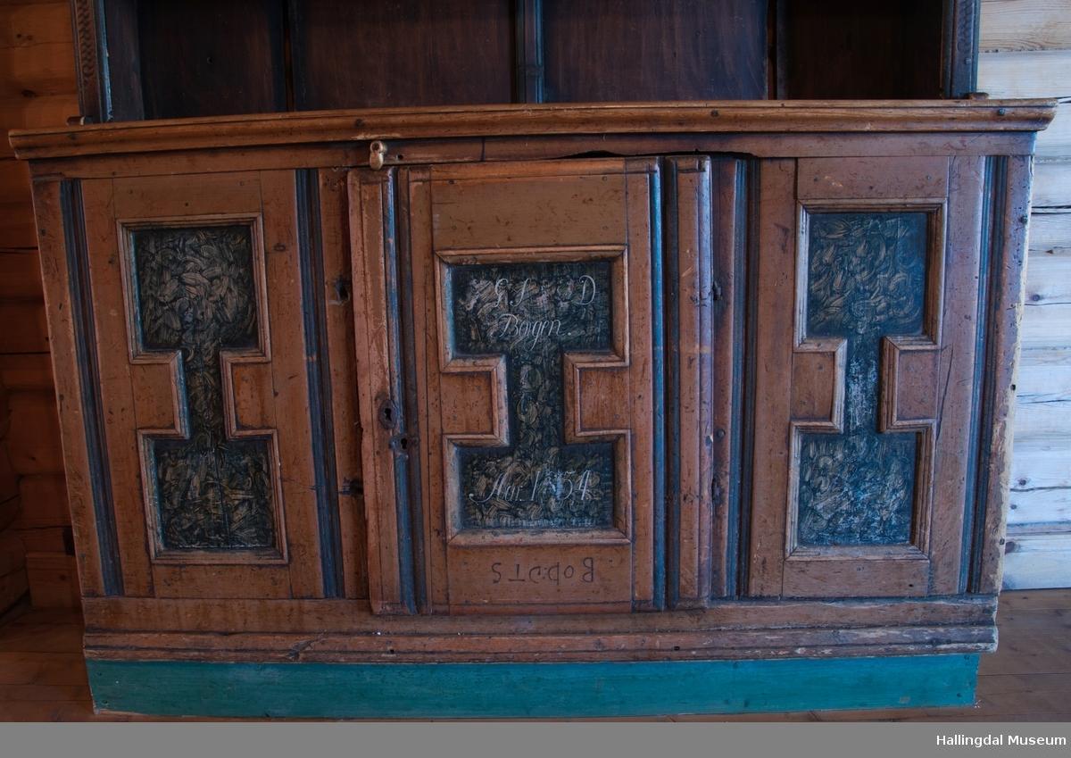 """Rester etter rød og blå maling.  Gesims, skråner ned bakover. Profilert. 6 sirkulære hull i arkitraven.  Mellom disse er malt med sorte bokstaver.  Gavlene har utskårne """"hylleknekter"""".  Bakveggen består av fire vertikale planker.  Skjøtene er dekket med profilerte lister.  Bare to biter i nederste del til venstre er fremdeles på plass.  Nederste del er lukket skap.  Tredelt, midterste del er skapdør.  Platen har profillist.  Feltene har speilfyllinger.  Blåmalte.  Klosset marmorering.  Speilfyllingenes form er som en liggen H.  Har profillist.  Skapet er satt på en ny grønmalt plate.  På døren er malt hvite bokstaver.  Nederst på døren er skåret inn bokstaver, opp-ned.  To nøkkelhull m. jernbeslag på venstre side av døren.  Over døren til venstre, en dreibar trekloss, holder igjen.  Innvendig har døren merke etter stort jernbeslag på samme side som nøkkelhullene.  To lister skåret i treverket minner om lange jernbeslag,-smalner mot nøkkelhullene.  Akantusranker i rødt, blått og hvitt, meget avslitt.  En hylle i skapet. Mangler bakvegg.  Karmen har på venstre side spor etter to jernhengsler.  Øverst på høyre kortside, mangler gesimsen en bit, og holdes til sideveggen med en jernkrampe.  Jernkrampe også på venstre side.  Skapplaten mangler list på høyre side.  Venstre side, fra gesimsen og ned har spor etter å ha stått inntil en vegg eller et annet møbel."""