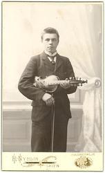 Andres T. Innleggen med hardingfele i fotografinteriør.