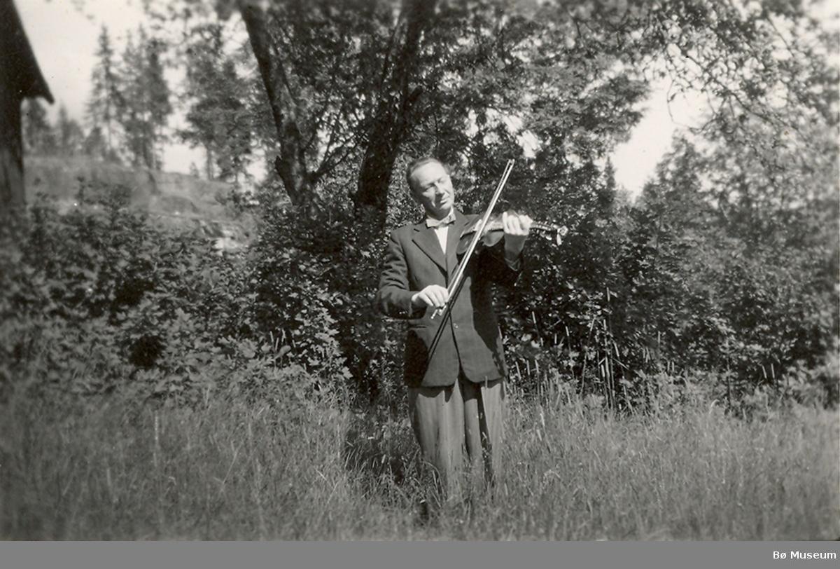 Jon Lunden (1903-1988) frå Bø spelar hardingfele ute i ein hage.