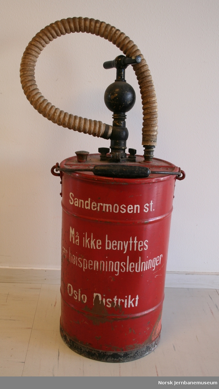"""Håndbetjent brannsprøyte. Påskrifter: """"Sandermosen st."""", """"Må ikke brukes nær høyspenningsledninger"""" og """" Oslo distrikt""""."""