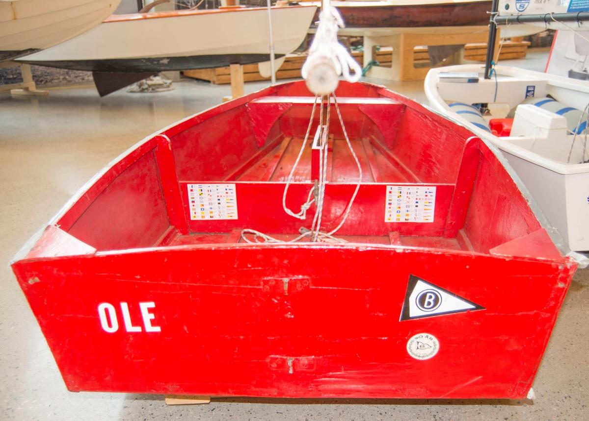 Rød A-jolle med diverse klistremerker på. Senkekjøl. Laget av huntonitt. Rigg og seil intakt, men ikke opprinnelig seil på jolla.