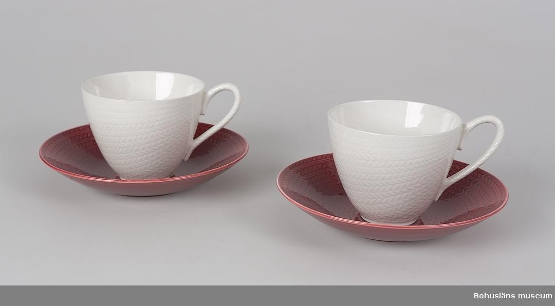 """Koppens mått: H. 8, Diam. 9,8 cm. Fat: H. 3,2 cm, diameter 17 cm. """"Blå eld"""", kopp vit, fat rött. Formgivare: Hertha Bengtsson. En variant av """"Blå eld"""" som inte var i produktion mer än sex år. Ibland kallas den """"Röd eld"""", men fabriken uppger själva att """"Blå eld"""" fanns i blå, röda, grå och vita delar."""