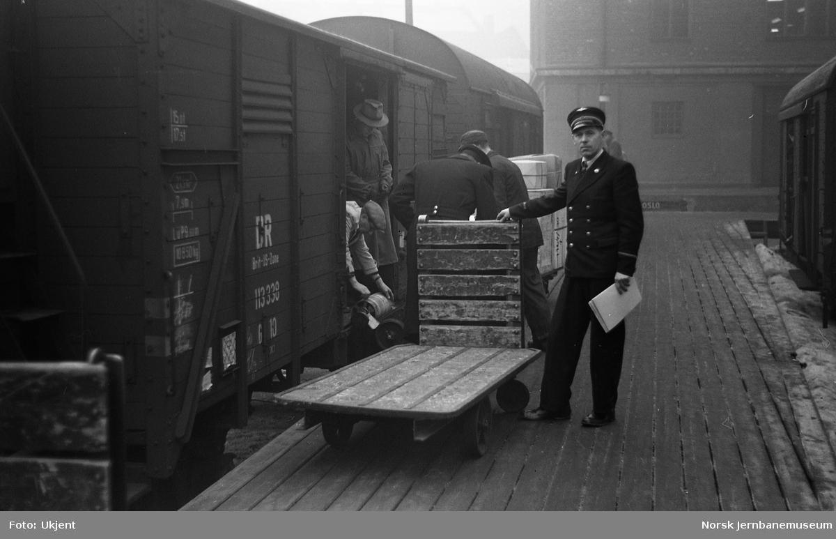 Mann med plattformtralle foran tysk lukket godsvogn