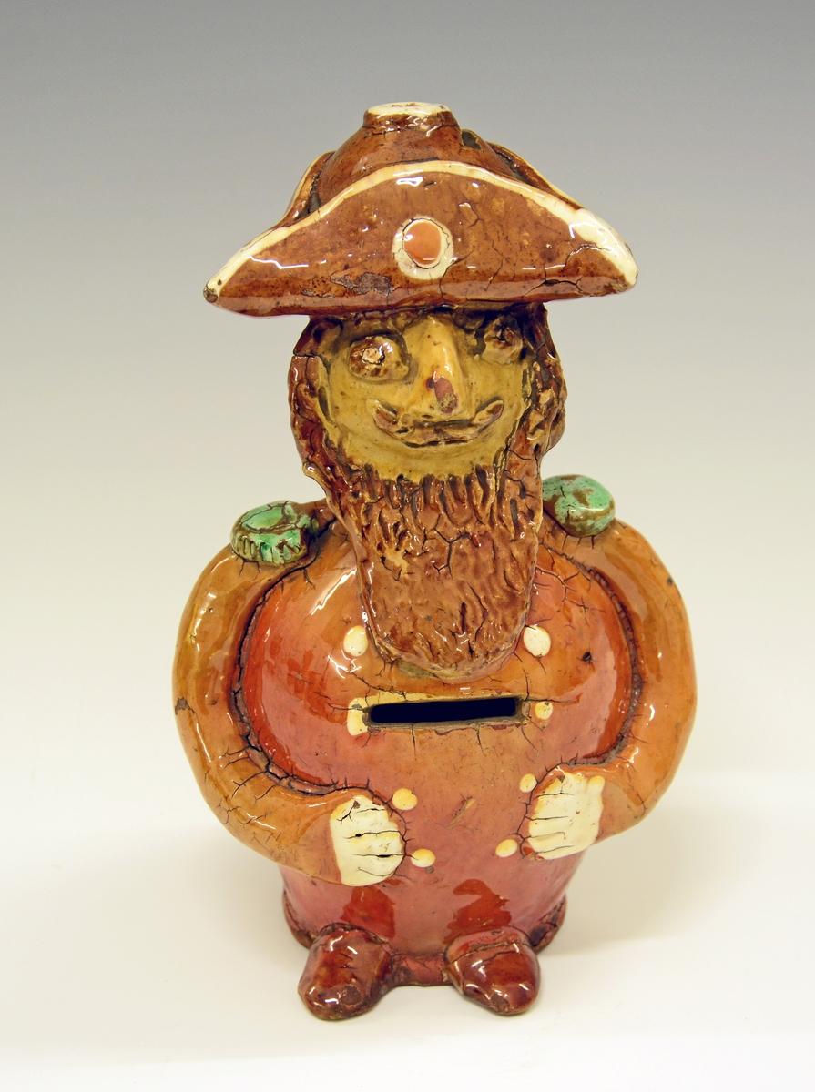 Fra protokollen: Sparebøsse i form av en tyk mand med trekantet hat paa hodet. Av glasert lertöi. Skal være fra Lunde potteri (Fossen?).